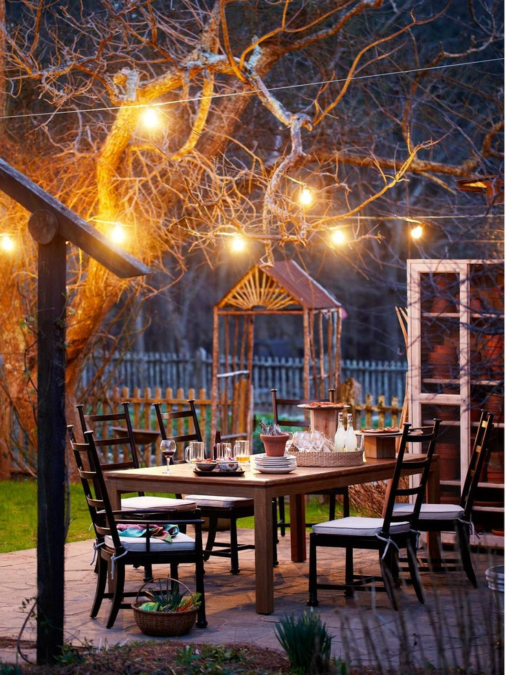 outdoor eating area at night  globe lights and a potting cupboard