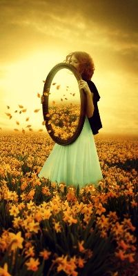 Girl with a mirror on a field of flowers