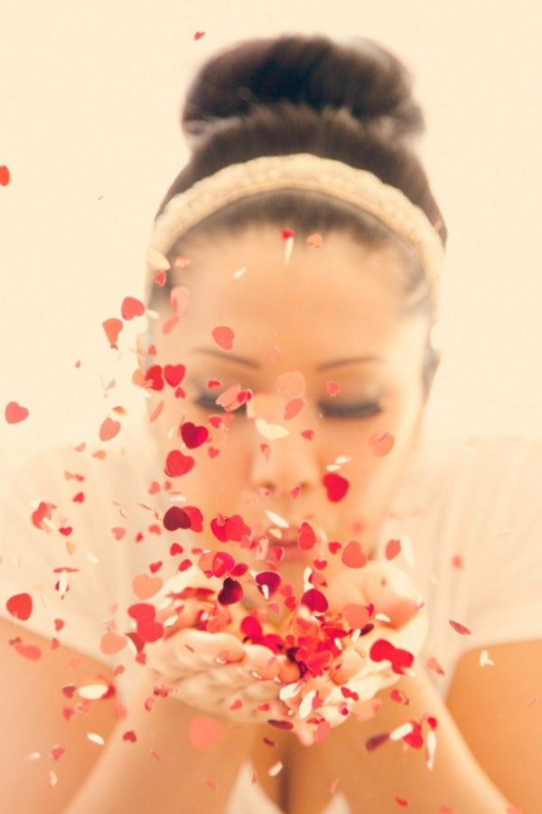 bride blowing red heart confetti might need someone to help drop confetti for a fuller look