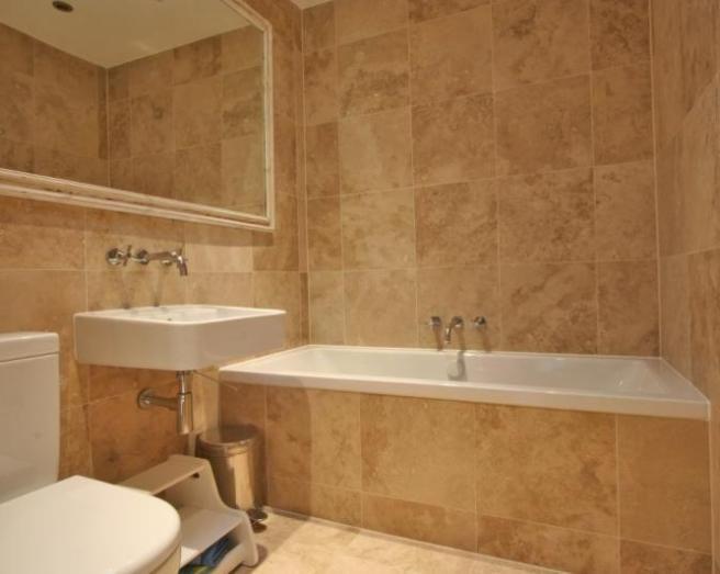 photo of modern beige brown orange bathroom with mirror tiled tiles