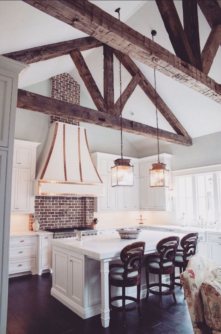 This kitchen provides a comforting and inviting feel. I love the use of the wood beams to highlight the ceiling design and the dark wood flooring to make the white casework stand out.