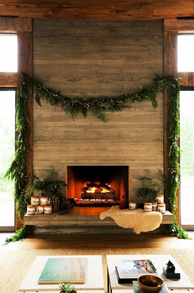 A wooden fireplace with hanging garland and cozy decorative accents