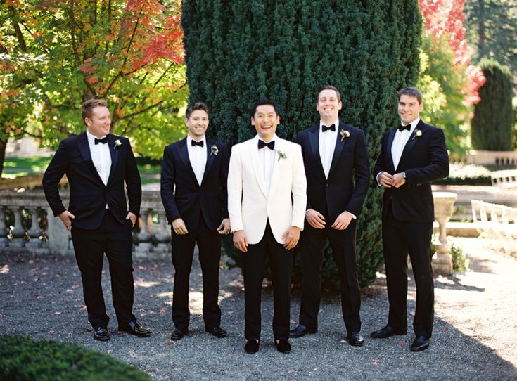 great groom style | classic black tuxedos for the groomsmen and a white jacket for the groom to stand out