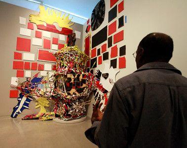 Description of . Artist Chris Johnson admires John McCoy's large scale sculptural installation piece at the