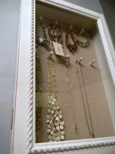 Purchase a shadow box with a glass door front and some decorative push pins.  Instant jewelry display case. :)