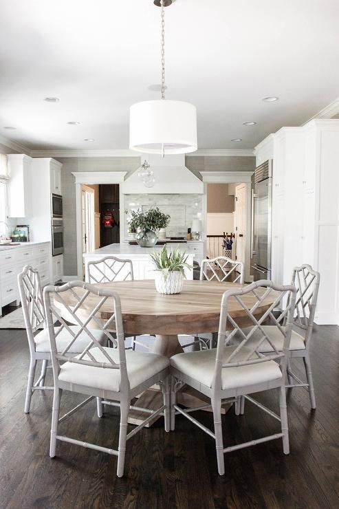 Open plan dining room located beside a large kitchen features a round salvaged wood dining table surrounded by gray bamboo dining chairs with white seat cushions illuminated by a white drum pendant lighting dark stained oak wood floors.