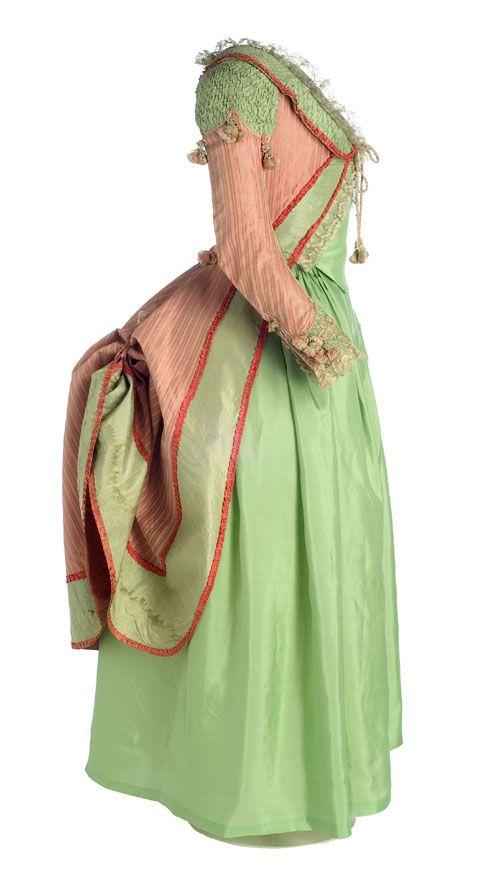 Polonesa Neoclasicismo, ca. 1775-1785 Polonesa en seda listada de color salmón y decoración a base de tejido aplicado en tafetán de seda verde. El escote, redondo en el delantero y con cuello vuelto. La manga, larga y estrecha, cierra en la muñeca con cinco botones cilíndricos forrados con hilos de seda. Las costuras van cubiertas por un cordón trenzado que termina a la altura de la cintura en lazo de pasamanería y borlón. Cuello, hombreras y puños están realizados en seda verde drapeada....