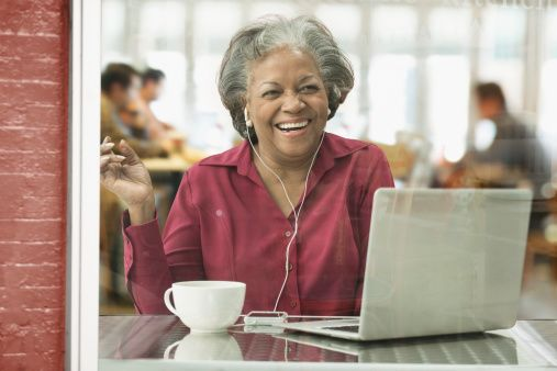 Black woman listening to headphones at cafe