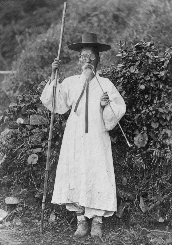 A Korean man in a traditional robe and boots, wearing a horse hair and bamboo hat