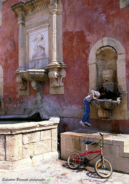 A child drinks from the Piazza fountain in Catania, Sicily