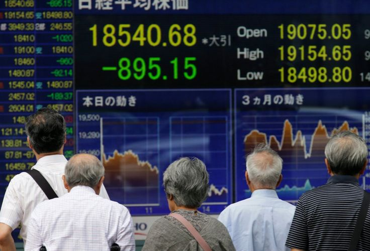 """Pedestrians in Tokyo looking at closing information for Tokyo's Nikkei Stock Average, after stocks t... - 8.24.15. """"why global stock markets are going crazy."""""""
