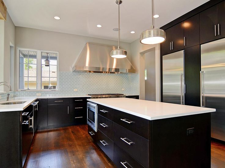 Black Cabinets With White Countertops Create A Striking Palette In This  Spacious, Modern Kitchen. Hardwood Floors And A Light Blue, Glass Tile  Backsplash ...