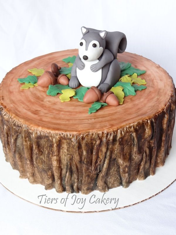 Tree stump cake with fondant squirrel and acorns on top.
