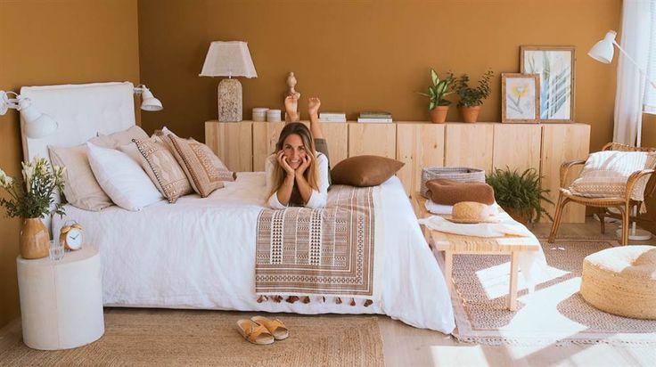 Chica tumbada sobre la cama en dormitorio color marrón caramelo con aparador y banqueta de madera, cabecero y sábanas blancas, puf y butaca de caña
