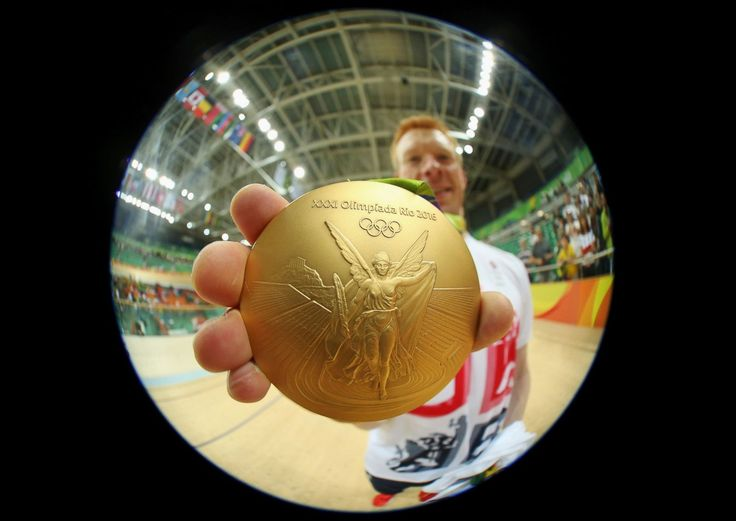Ed Clancy of Great Britain poses with his gold medal from cycling, Aug. 12…