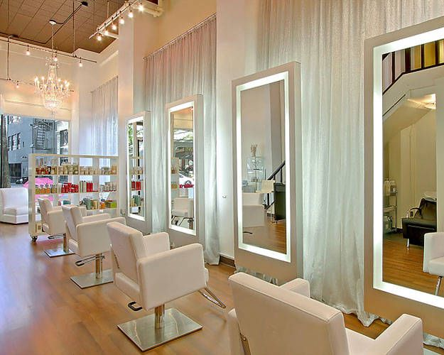 In this glam salon, sheer silver fabric curtaining the walls brings an iridescent shimmer to the room—and adds a soft touch to illuminated freestanding mirrors.