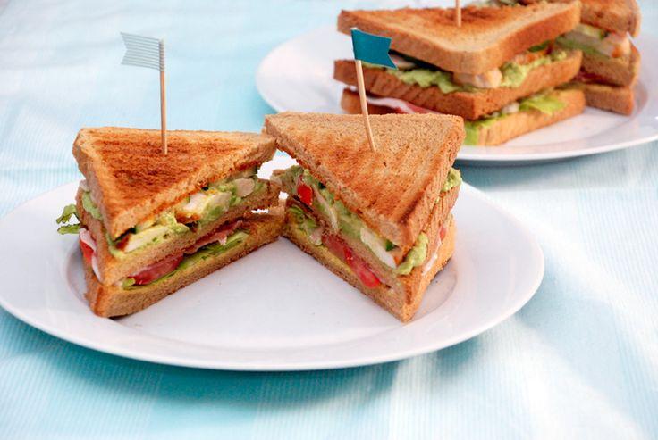 Club sandwiches med kylling, bacon, grøntsager og tre slags dressing.