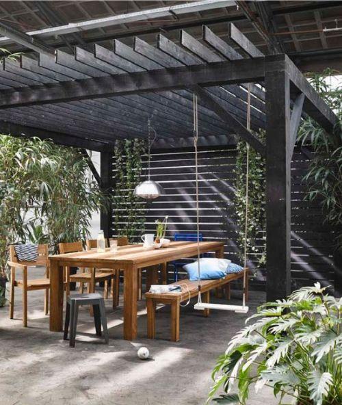 Grote houten tuintafel en schommel op terras - bekijk en koop de producten van dit beeld op shopinstijl.nl