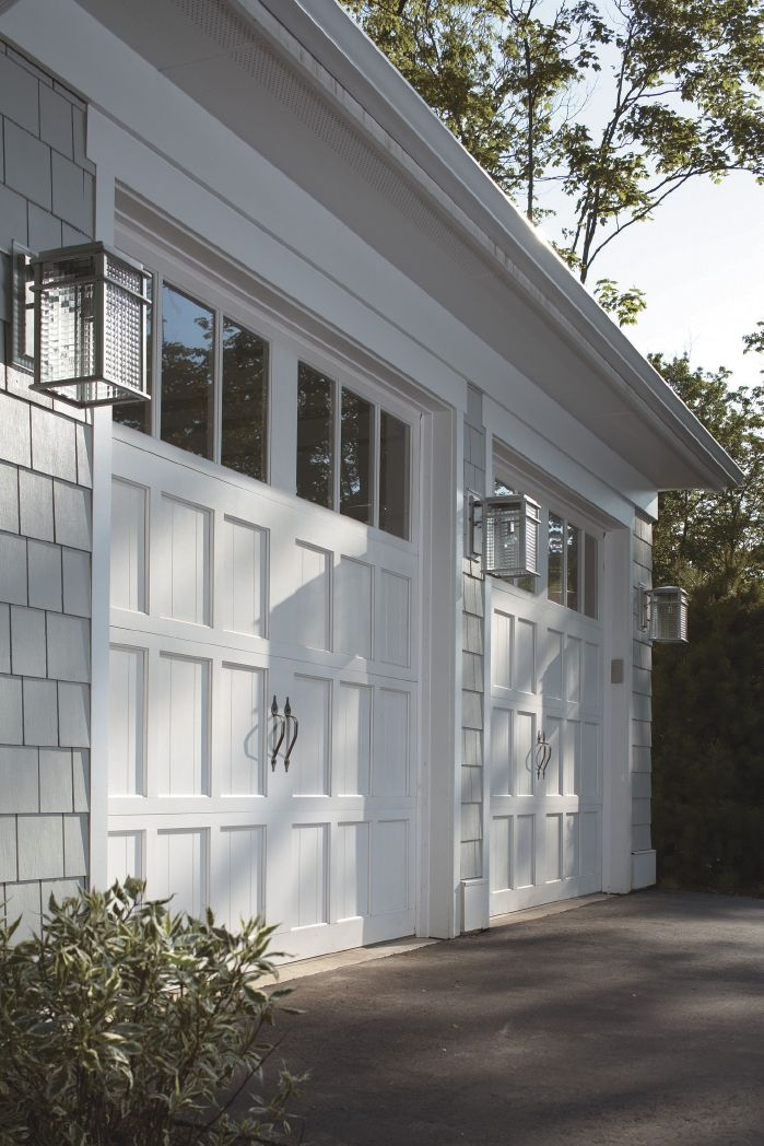 "These Clopay Reserve Collection wood carriage house garage doors were featured on Midwest Living magazine's Idea House in Egg Harbor, WI, also known as the ""Cape Cod"" of the Midwest. We love how the light fixtures echo the shape of the windows and panel design of the doors. Model shown: Design 3, REC13 windows factory painted white. www.clopaydoor.com."