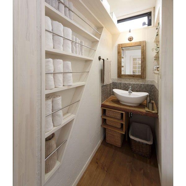 洗面室の壁に、棒付きの棚を設置。丸めて立てて見せる収納。