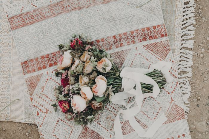 Dusty-rose inspired color palette with rustic tapestries, blush florals and an ethereal white ribbon | image by Lizztin Photography