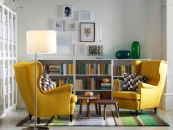 Lys stue med to gule ørelappstoler, to settbord i valnøttfiner, hvite åpne bokhyller og bokhyller med vitrinedører.