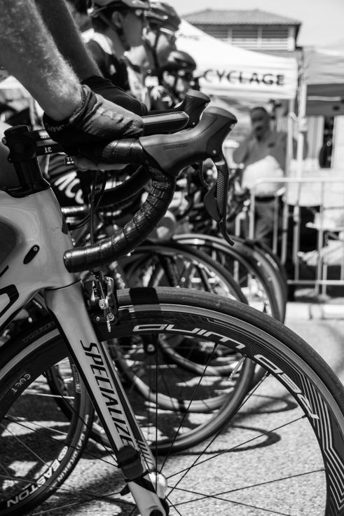L3M2AP1 ISO200 38mm 1/800th sec f/5.6. Nikon D7100. Handheld on a sunny morning. Shot from the 'hip', dangling from my leg. I took several frames between the bars separating spectators from the racers lined up. I find the black and white draws attention to the lines and curves, rather than the colours distracting the eye.