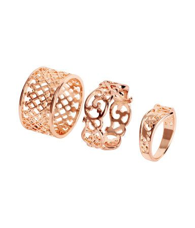 Rings in metal in various sizes and designs for wear on both upper and lower parts of fingers.