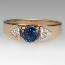 This lovely estate ring features a 1/2 carat blue sapphire center stone set in a six-prong head. The sapphire is accented with diamonds set in triangle shapes on each side. The ring is crafted of solid 14k yellow gold and the sapphire is very pretty.