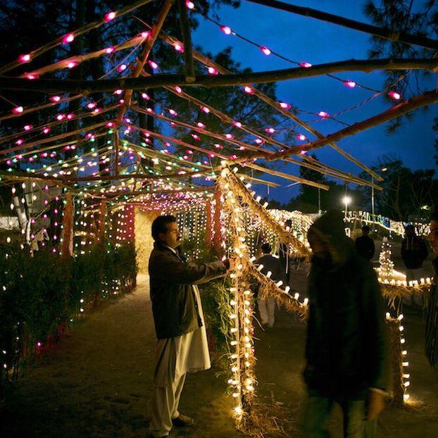 Un gruppo di persone decora una strada con delle luci in occasione delle feste di Natale a Islamabad, Pakistan