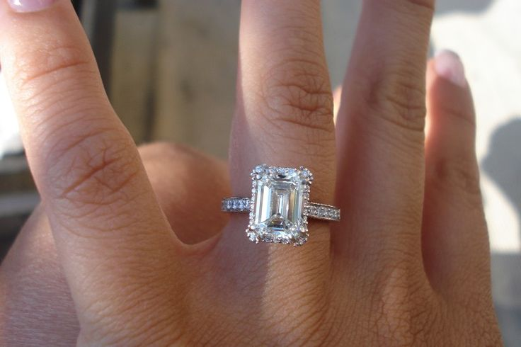 Emerald cut engagement rings on finger