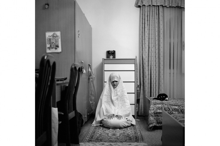 Tripoli, Libya. April 2012    A Libyan woman prays in her bedroom. When Muslims pray they present themselves to God in the act, to be fully covered is a mark of respect.