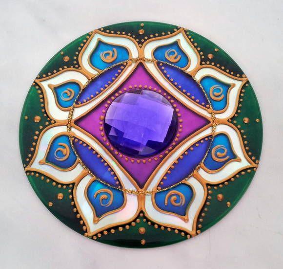 Mandala em CD reciclado, pintura vitral, decorado com tinta relevo dourada e uma pedra acrílica no centro. Possui gancho de metal para ser pendurada na parede. R$ 18,00