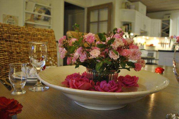 Stil en vase med en buket roser i et fad med vand og lad nogle rosen hoveder flyde rundt om vasen - Place a vase with a bouquet off roses in a bowl with water and let some rose heads float around the vase