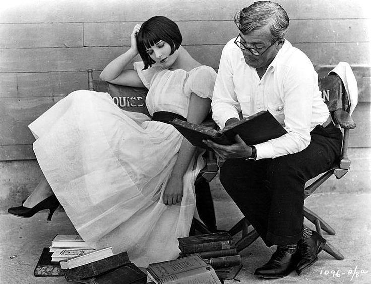 American actress Louise Brooks reading a script with author Keene Thompson on the set of 'Now We're In the Air', 1927.
