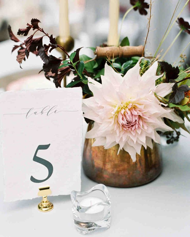 Spring Wedding Ideas from Real Celebrations | Martha Stewart Weddings - A single dahlia dressed up a greenery-filled vintage teapot, which the couple paired with deckle-edged table number cards for elegant table decor. #weddingideas #tablenumbers #weddingflowers
