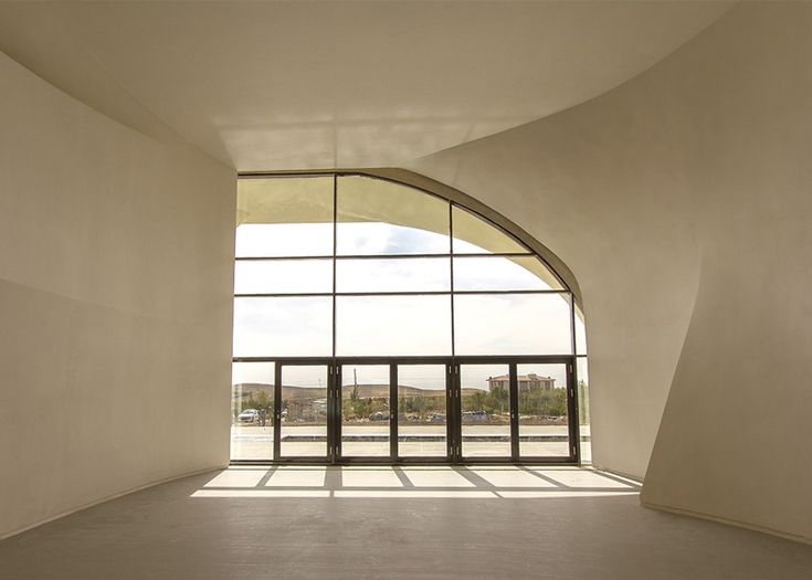Billowing curves sweep across the concrete facade and continue inside this house near Tehran