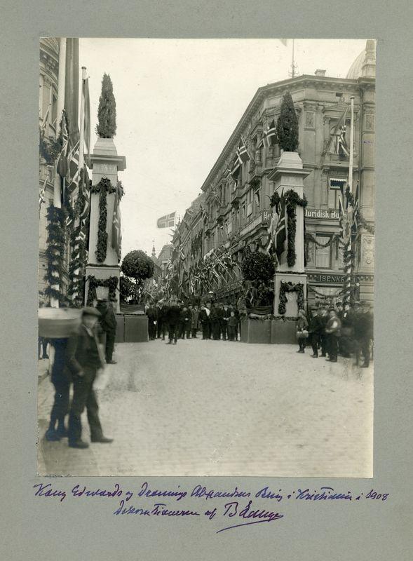 Fra kong Edward VII og dronning Alexandra sitt besøk i Kristiania i 1908. Publikum og tilskuere langs Karl Johans gate. Æresportal, girlander og flagg langs kjøreruten til de kongelige