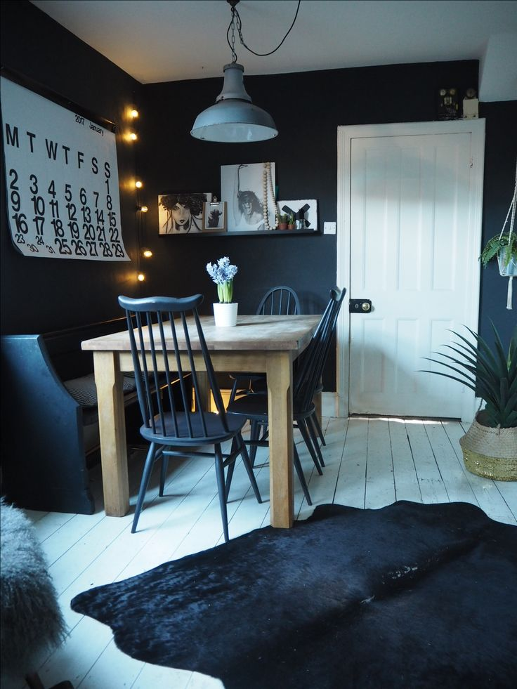 Dark coloured dining room painted in Farrow and Ball off black with oak dining table, Ercol chairs and cowhide rug over white painted floorboards.