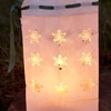 Light up a walkway with a snowflake motif luminaria. Use a snowflake paper punch to create the designs on a paper bag. Punch holes in the top edge of the bag and weave ribbon through the holes. Fill the bags with sand or aquarium rocks for weight. Add a candle and watch the light shine through the design.  Editor's Tip: Never leave lit candles unattended. Use battery-operated candles if you cannot monitor the lit luminaria.