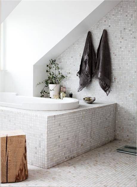 I love the subtle colours of the mosaic tiles and the way the seal coloured towels with tassels look like artworks on the wall.