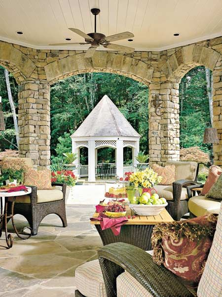 This outdoor room's substantial look comes from the stone floor, wood-paneled ceiling, and arched openings. Chocolate brown wicker furniture blends in with the natural materials. From the outdoor room, you step down to a terraced pool area where your eye is drawn to a white gazebo. (Photo: Photo: Lisa Powell; Stylist: Lisa Powell)