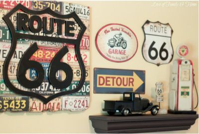 Gallery wall art display in a baby boy's Route 66 nursery theme including vintage road signs and service station memorabilia
