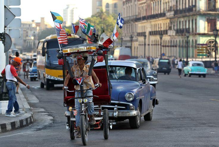 CUBA. Un bicitaxi adornado con varias banderas, entre ellas una de EE.UU., circula por una calle de La Habana el martes 31 de marzo de 2015. EFE/Alejandro Ernesto