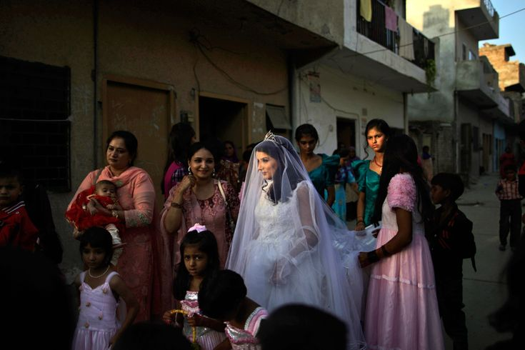 Pakistani bride Shabana Gill (20) is flanked by her friends while waiting for family members to go to a church to attend her wedding procession in a Christian neighborhood in Islamabad, Pakistan, on Oct. 5. (Muhammed Muheisen/Associated Press)