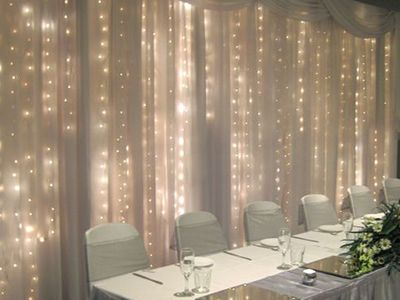 Pipe and drape with twinkle light curtains. **$75 for a 10′ segment of shear drape with twinkle lights behind. Or $6 per foot of just drape.