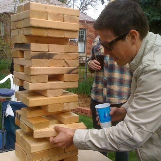 """To make a DIY outdoor version of Jenga get out some 2x4's and cut them into approx 10 ½ """" long pieces. Once you have 54 pieces, sand them up a little, stack 'em, and challenge everyone to a match!    Our favorite bar has one of these on the patio -- giant jenga! Super fun!"""