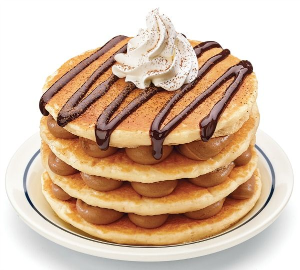Tiramisu Pancakes - bttermilk stacks with layers of mocha cream topped with a generous drizzle of chocolate, whipped cream and a dusting of cocoa powder.