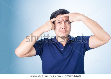 Handsome Asian man Squeezing pimple, acne, on blue background