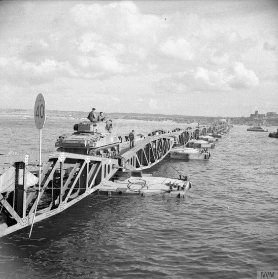 "A Sherman tank of the ""B"" Squadron 1st Armoured Regiment (10th Armoured Cavalry Brigade 1st Polish Armoured Division) commencing its journey to shore along a floating bridge at Arromanches 26-28 July 1944."